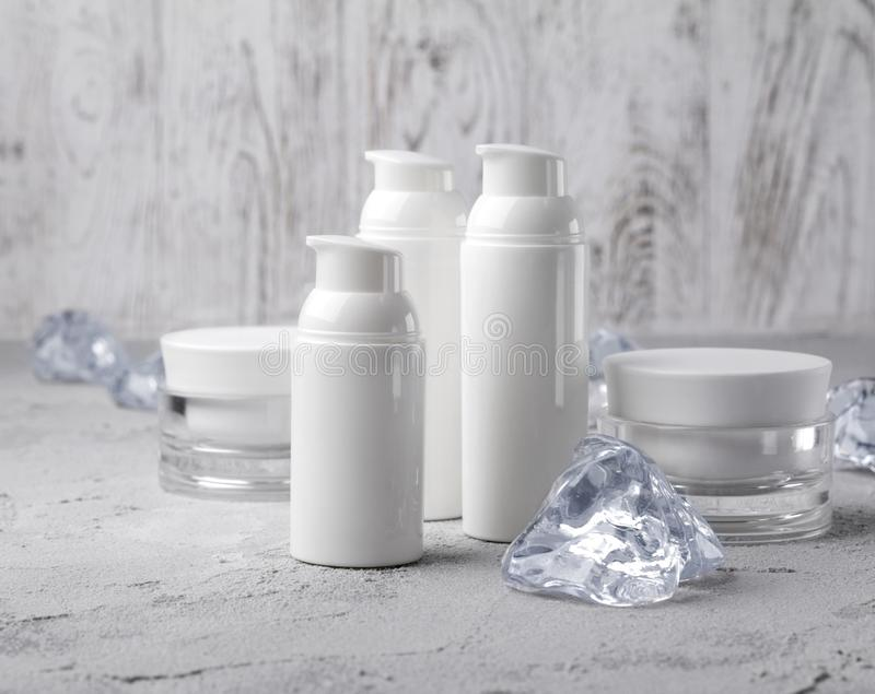 Set of cosmetic cream bottles with ice on gray table royalty free stock photography
