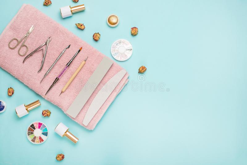 A set of cosmetic tools for manicure and pedicure on a blue background. Gel polishes, nail files and nippers and top view. royalty free stock photography