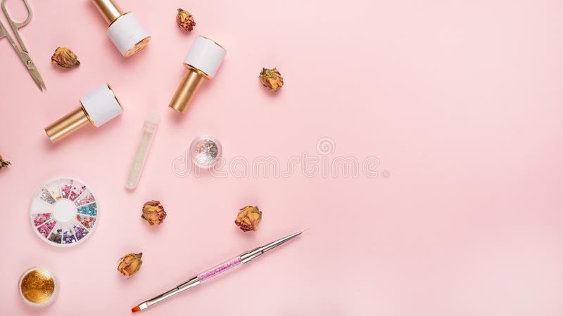 A set of cosmetic tools for manicure and pedicure on a pink background. Gel polishes, nail files and nippers and top view. royalty free stock photography