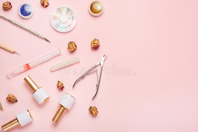 A set of cosmetic tools for manicure and pedicure on a pink background. Gel polishes, nail files and nippers and top view. Composition for a card with a place stock photo