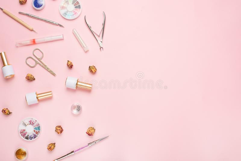 A set of cosmetic tools for manicure and pedicure on a pink background. Gel polishes, nail files and nippers and top view. Composition for a card with a place stock image