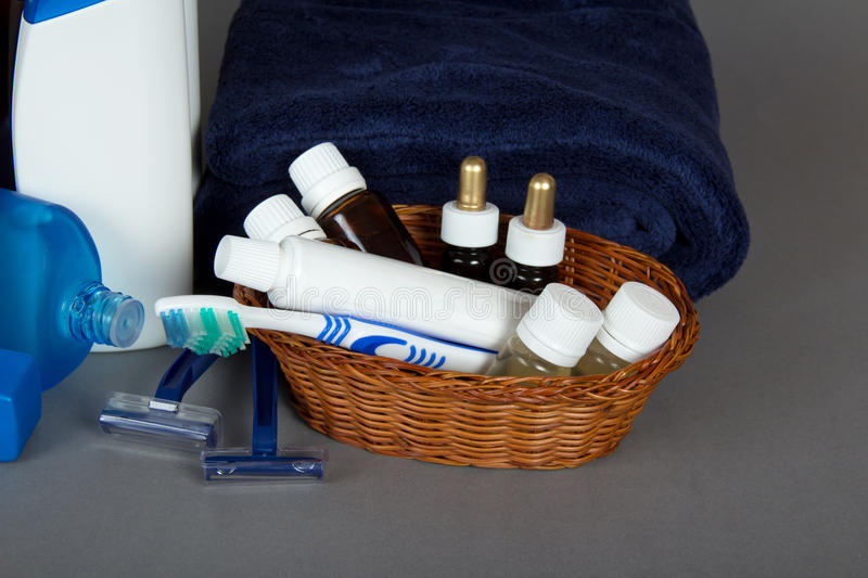 Set of cosmetics in basket, toothbrush and paste. Set of cosmetics in a basket, a toothbrush and paste, a towel on a gray background royalty free stock photo