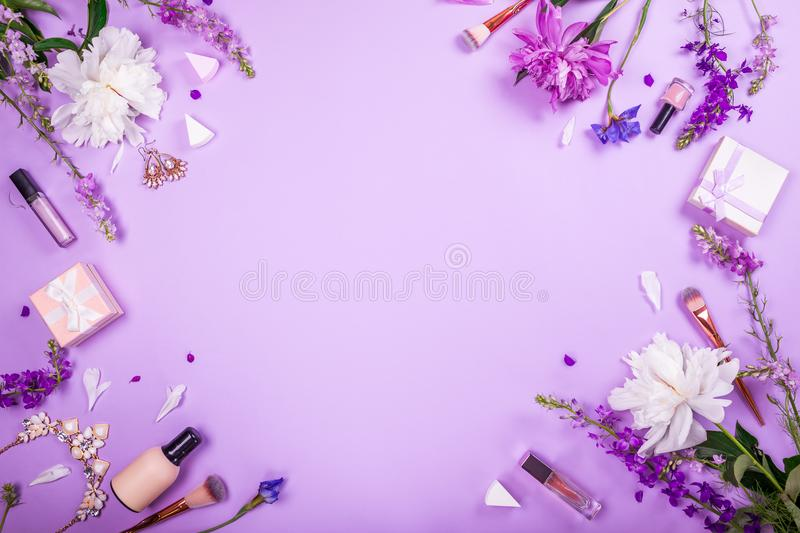 Set of cosmetics, brushes and jewellery with fresh flowers on purple background. Summer sale. Shopping stock photos