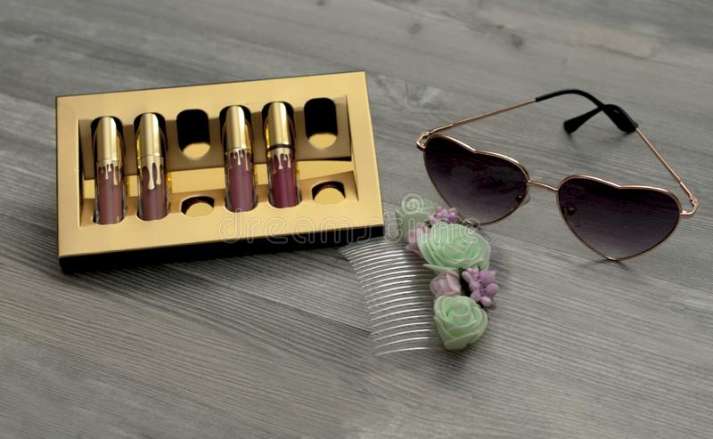 Set of cosmetics: lipstick glasses background, costume jewelry royalty free stock images