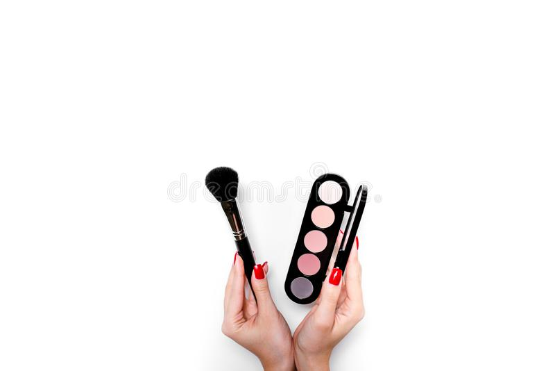 Set of cosmetics for makeup and brush in female hands isolated on white background. royalty free stock photo