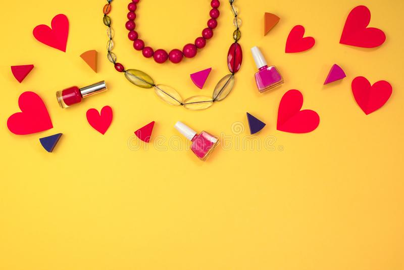 Set of cosmetics women's accessories jewelry Red heart on yellow background concept of Valentine's day. Set of cosmetics women's accessories stock images