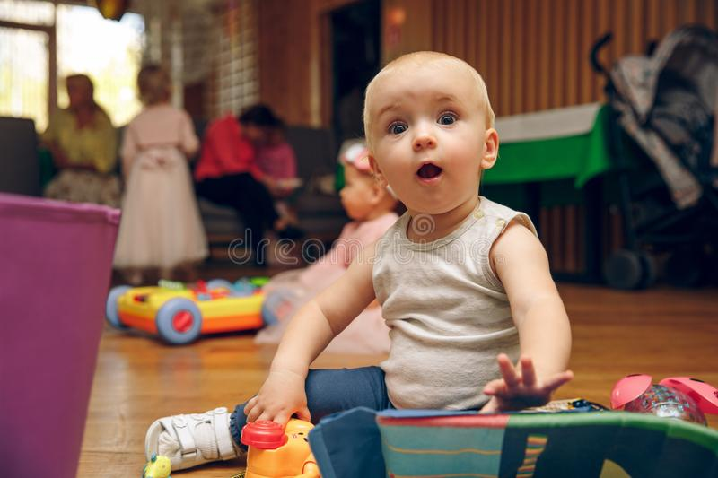 Set of crawling babies or toddlers with toys. surprised child plays with toys royalty free stock photo