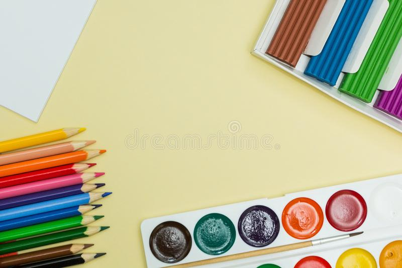 A set for creativity and drawing: watercolor paints, plasticine and multicolored pencils on a yellow background. Top view royalty free stock photos