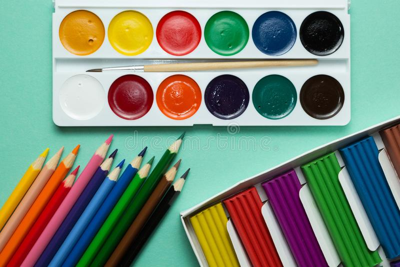 A set for creativity and drawing: watercolors, plasticine and multicolored pencils on a green background. Top view.  royalty free stock images