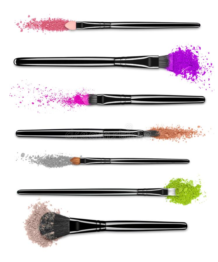 Set of crushed colored eyeshadows with brushes close-up stock photo