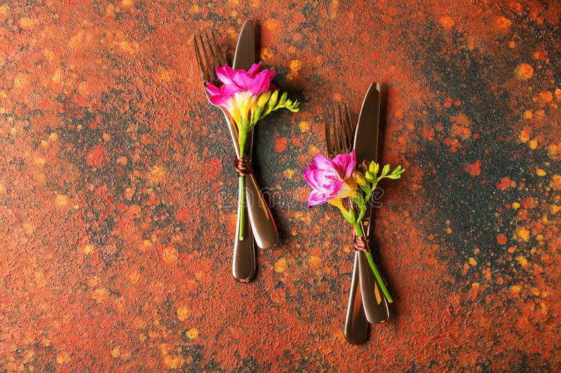 Set of cutlery with flowers on color background stock photos