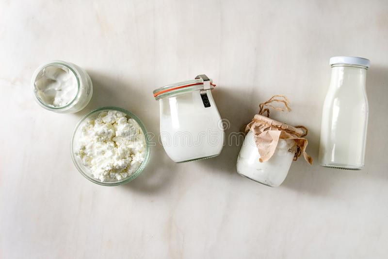 Set of dairy produce. Set of farm dairy produce cottage cheese, milk cream, plain yogurt in reusable eco friendly glass jars and bottle in row over white marble royalty free stock photos