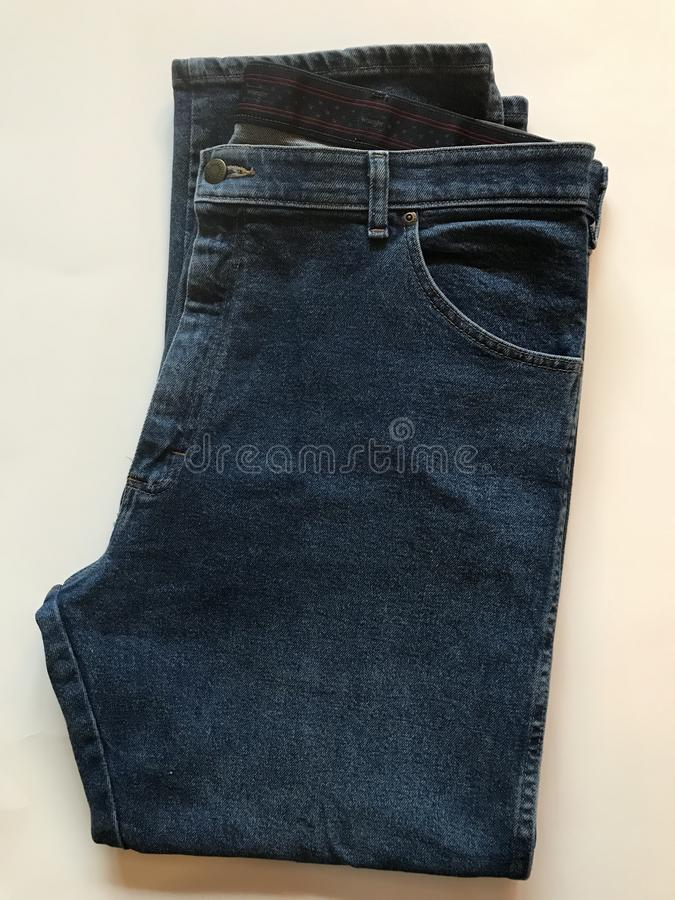 A set of dark jeans folded on a white background. Jeans are a type of pants or trousers, typically made from denim or dungaree cloth. Often the term `jeans` stock photos