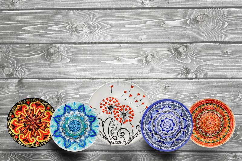 Set of decorative ceramic plates hand painted dot pattern with acrylic paints on a gray wooden background. Copy space stock image