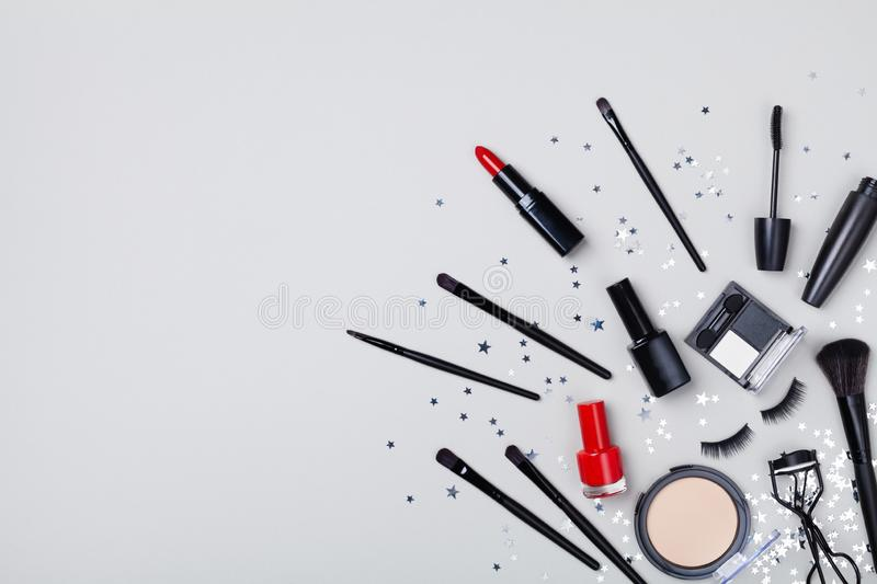 Set of decorative cosmetic and beauty products for makeup on star confetti background top view. Flat lay royalty free stock photos