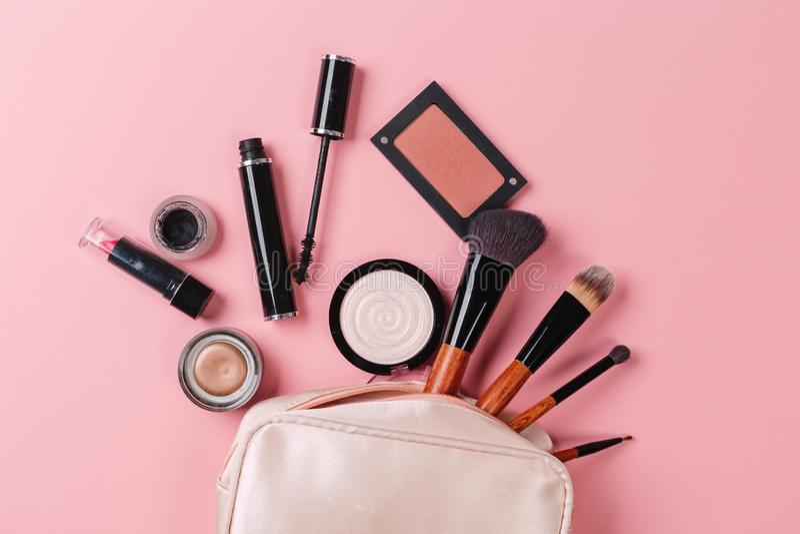 Decorative cosmetic powder, concealer, eye shadow brush, blush, foundation on pink background royalty free stock images