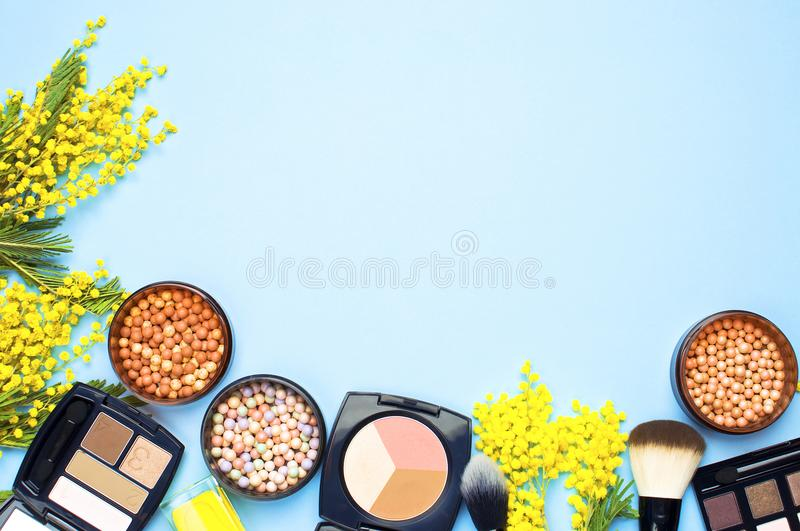 Set of decorative cosmetics for make-up Powder Rouge Eyeshadow Corrector Brushes and flowers of mimosa on blue background. Makeup royalty free stock photo