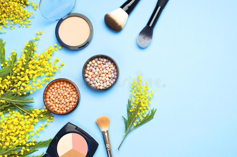 Set of decorative cosmetics for make-up Powder Rouge Eyeshadow Corrector Brushes and flowers of mimosa on blue background. Makeup royalty free stock photos