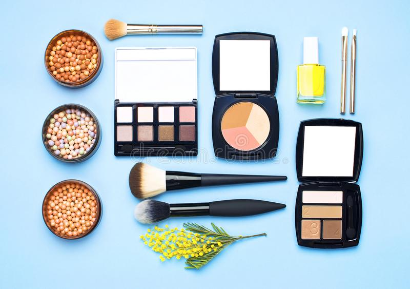 Set of decorative cosmetics for make-up Powder Rouge Eyeshadow Corrector Brushes and flowers of mimosa on blue background. Makeup stock photos