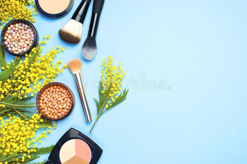 Set of decorative cosmetics for make-up Powder Rouge Eyeshadow Corrector Brushes and flowers of mimosa on blue background. Makeup stock images