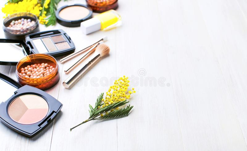 Set of decorative cosmetics for make-up Powder Rouge Eyeshadow Corrector Brushes and flowers of mimosa on a light wooden backgroun stock photos