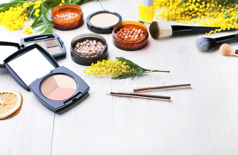 Set of decorative cosmetics for make-up Powder Rouge Eyeshadow Corrector Brushes and flowers of mimosa on a light wooden backgroun stock image
