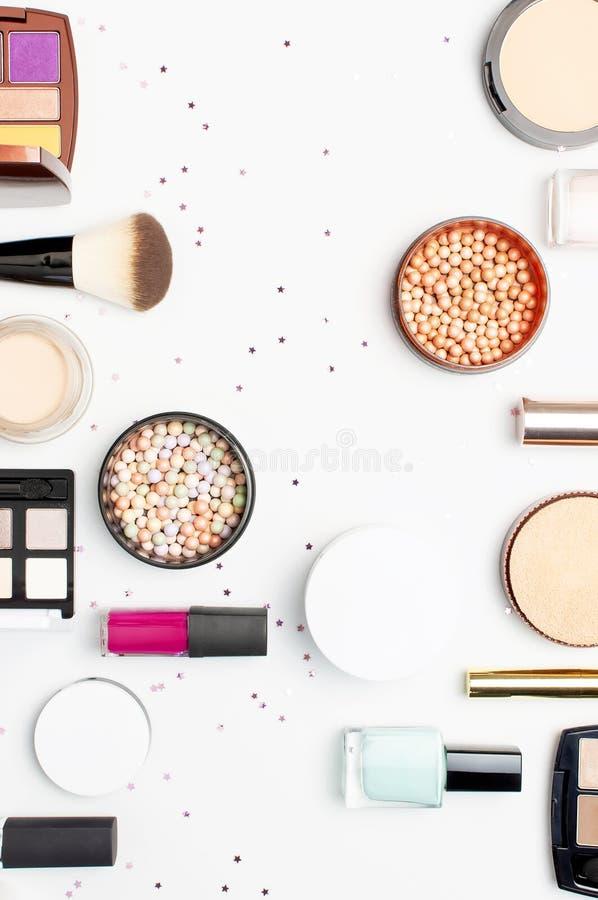 Set of decorative cosmetics mascara powder lipstick eyeshadow blush makeup brush, star confetti on light background top view Flat royalty free stock photos