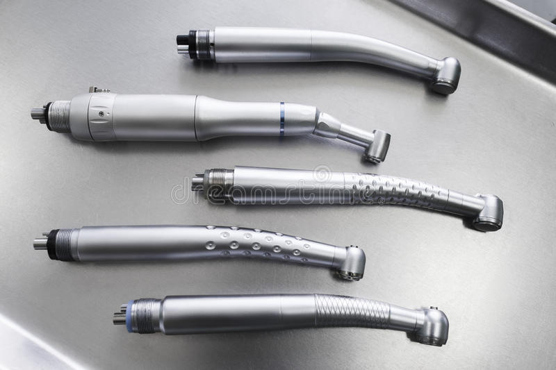 Set of dental handpieces without burs flat lay. Set of dental turbine handpieces without burs flat lay. Top view on set of dental turbine handpieces on metal stock photo