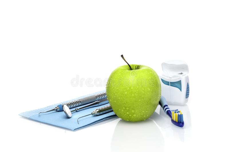 Set of dentist medical equipment tools with fresh green apple dental health care conceptual background image.- Image royalty free stock images