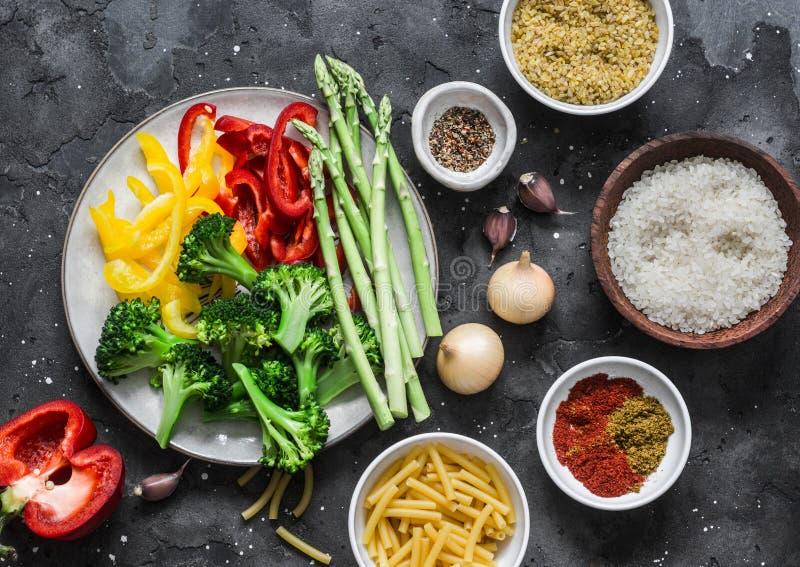 Set di prodotti per i pranzi vegetariani - pasta, riso, bulgur e verdure fresche su sfondo scuro, vista dall'alto immagini stock libere da diritti