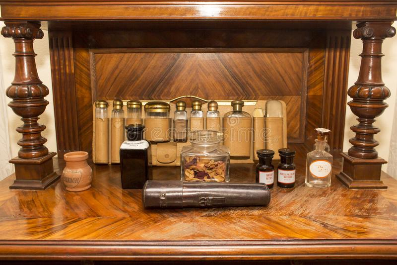 A set of different antique bottles made of dark and transparent glass in special cases, on the chest of drawers stock images