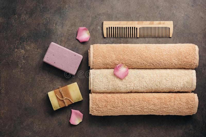 A set of different bath accessories, terry towels roll, wooden comb, handmade soap on a dark brown rustic background decorated. With rose petals. Flat lay, view stock photography