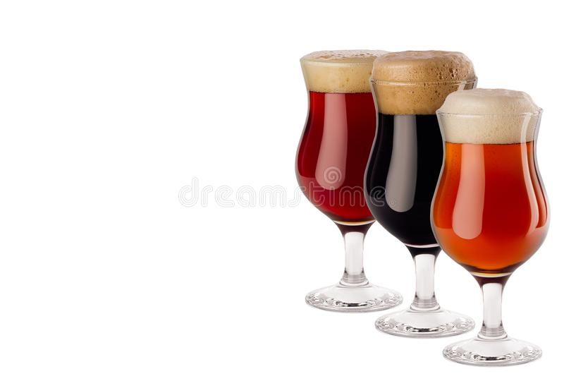 Set of different beer in wineglasses with foam - lager, red ale, porter - isolated on white background. Set of different beer in wineglasses with foam - lager royalty free stock images