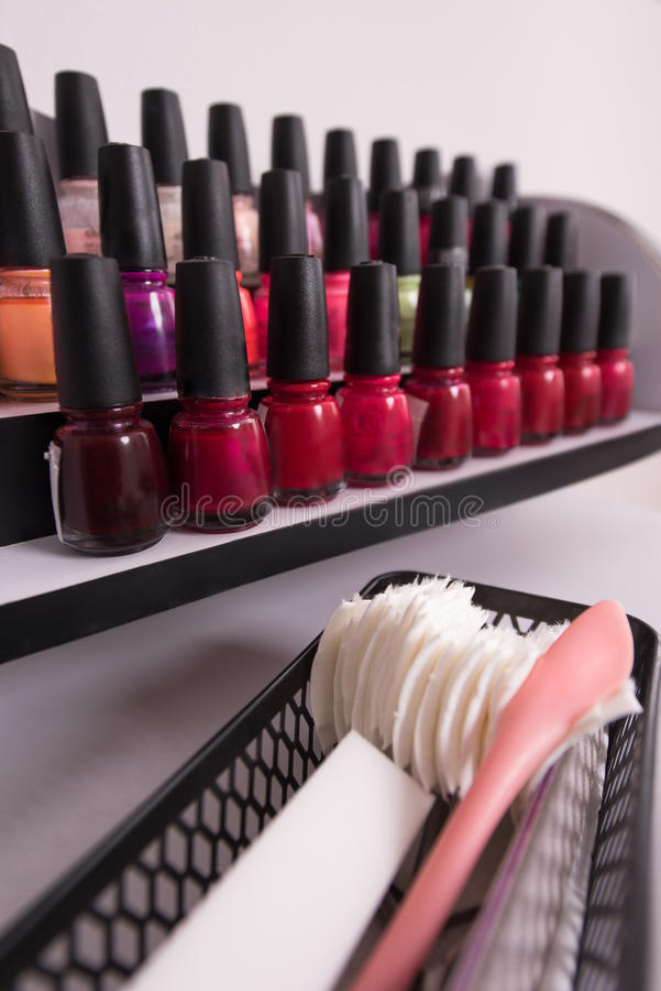 Set of different bottles of nail polish. In the shelf in the beauty salon stock images