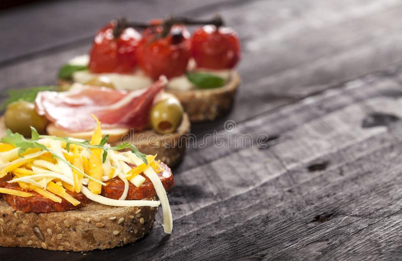 Set of different bruschettas on dark wooden table. Front view and copy space. royalty free stock photography