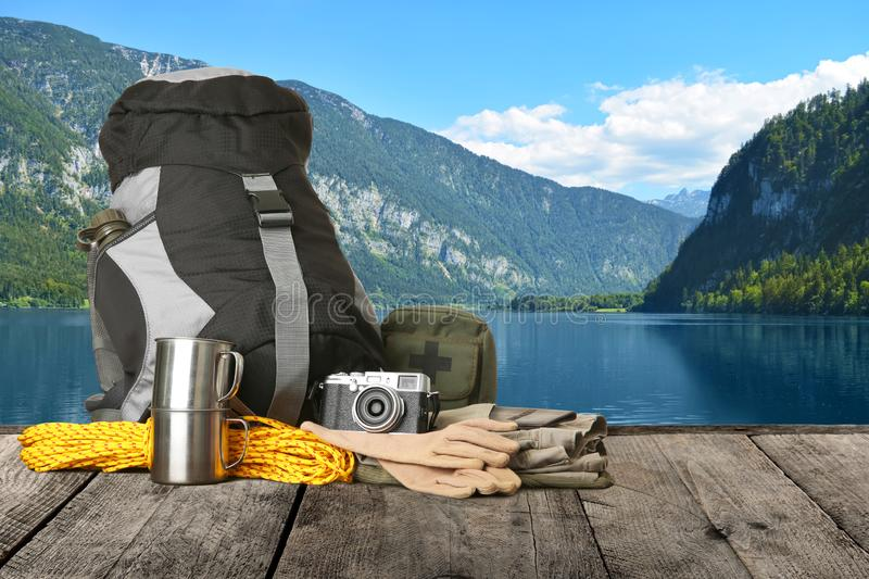 Set with different camping equipment on wooden table in mountains near river. Space for text royalty free stock image