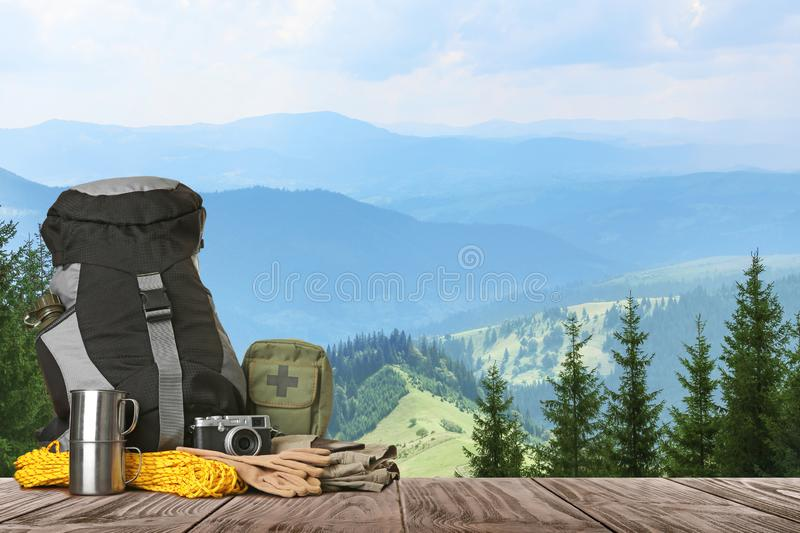 Set with different camping equipment on wooden table in mountains. Space for text royalty free stock image