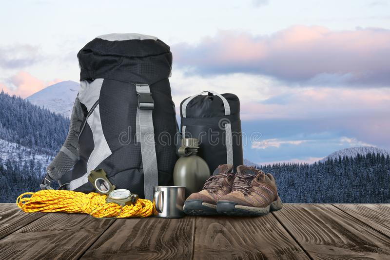 Set with different camping equipment on wooden table. In snowy mountains royalty free stock photo