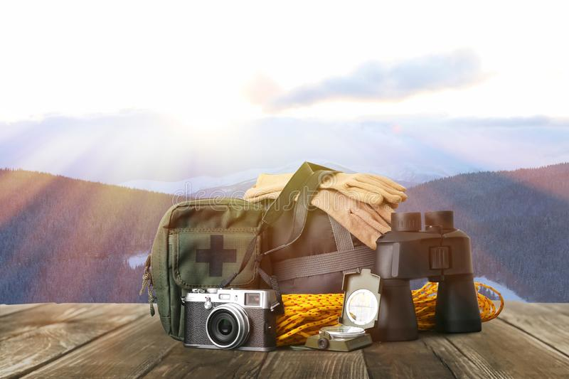 Set with different camping equipment on wooden table in mountains. Set with different camping equipment on wooden table in snowy mountains royalty free stock images
