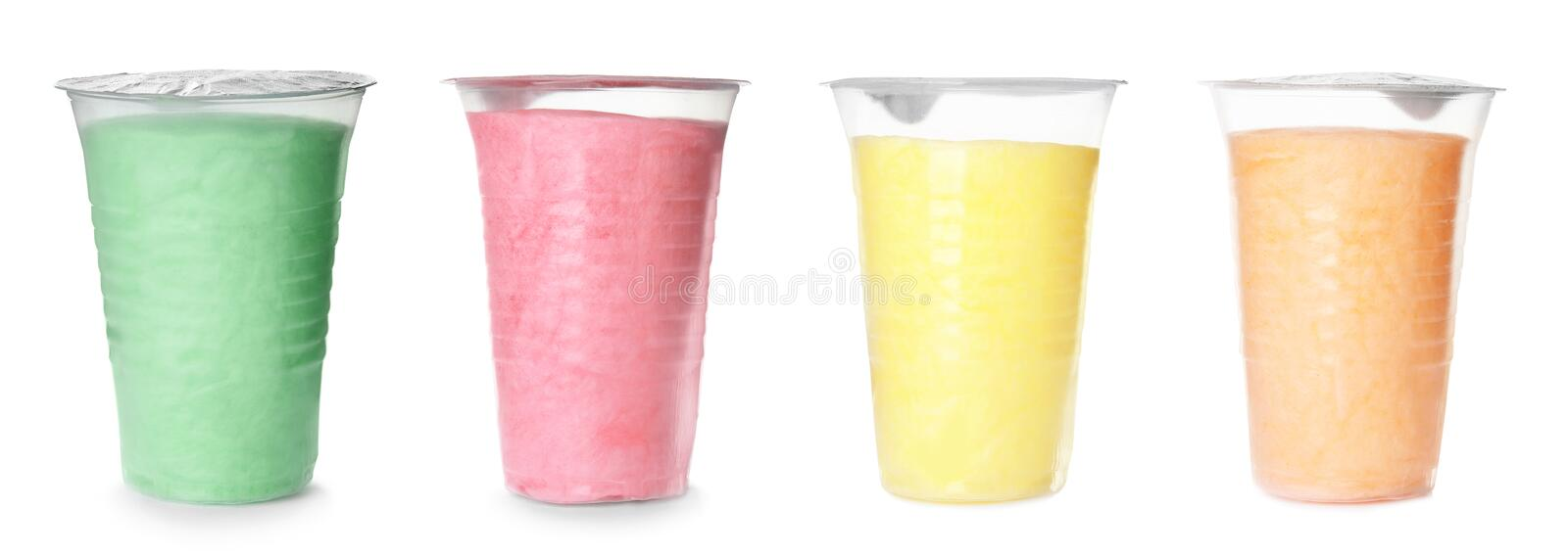 Set of different colorful yummy cotton candy in plastic cups on white royalty free stock photography