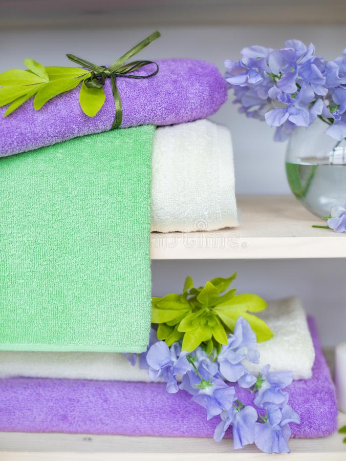 Set of different colors terry towels with blue flowers and candles on wooden shelfs royalty free stock image