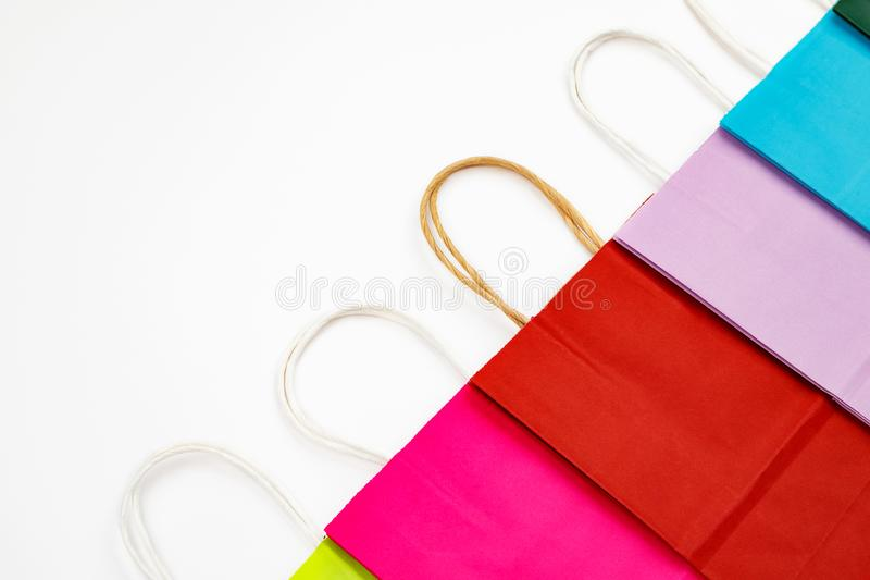 Set of different colour shopping paper bags on a white background, side view. Colorful, flat, buy, gift, present, purchase, retail, sale, package, container stock image