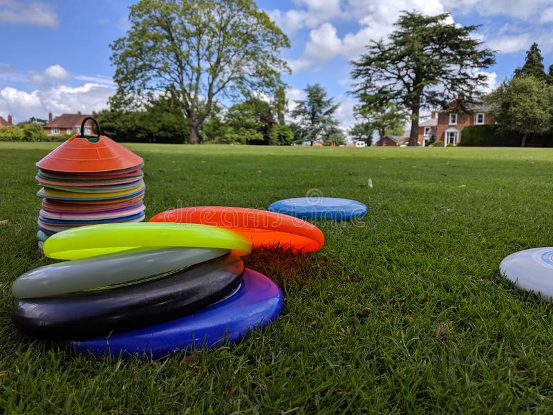 A set of different coloured ultimate frisbees piled up on the grass royalty free stock images