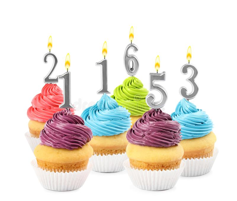 Set of different delicious birthday cupcakes with burning candles on white. Background royalty free stock photos