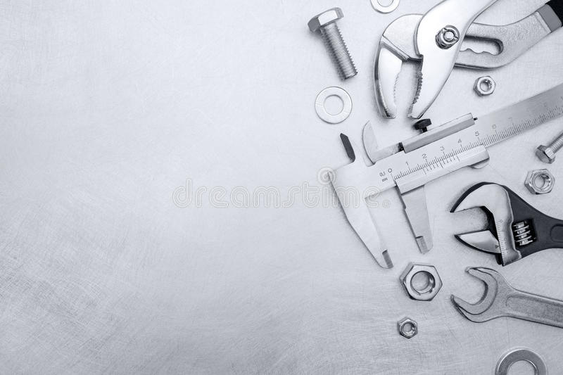 Set of different hand work tools including wrenches pliers and c. Aliper on grey brushed metal royalty free stock photos