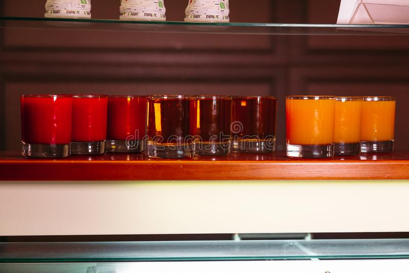 Set of different juice and cocktails on self in bar. royalty free stock images