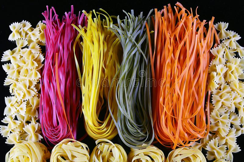 Set of different kinds of colorful Italian pasta, on a black background, healthy food concept, close-up stock photography