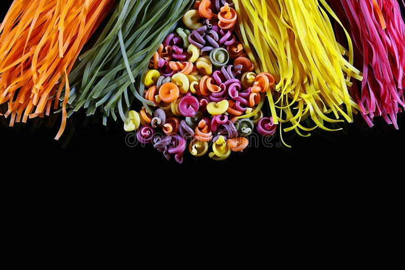 Set of different kinds of colorful Italian pasta, on a black background, healthy food concept, close-up, place for text royalty free stock image