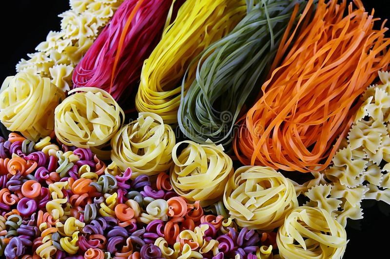 Set of different kinds of colorful Italian pasta, on a black background, healthy food concept, close-up stock photos