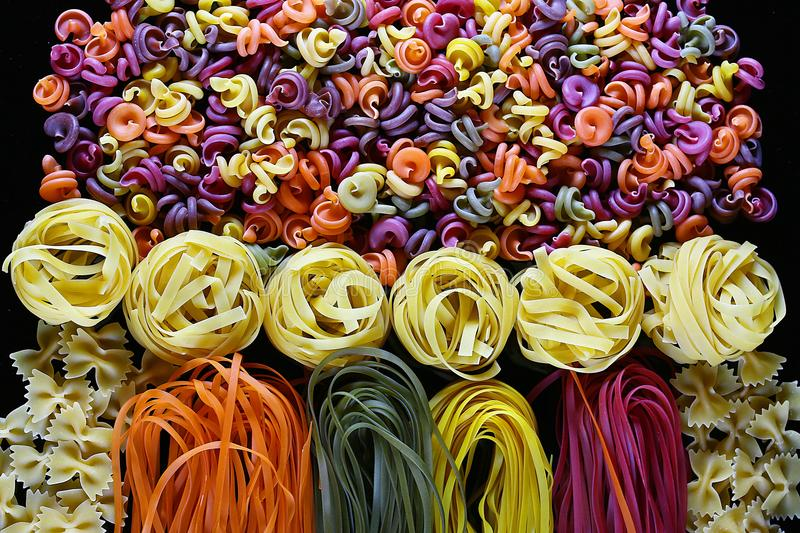 Set of different kinds of colorful Italian pasta, on a black background, healthy food concept, close-up stock images